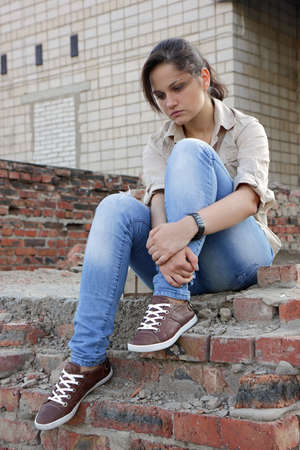 ordeal: Sad young woman sitting on the destroyed wall of the building