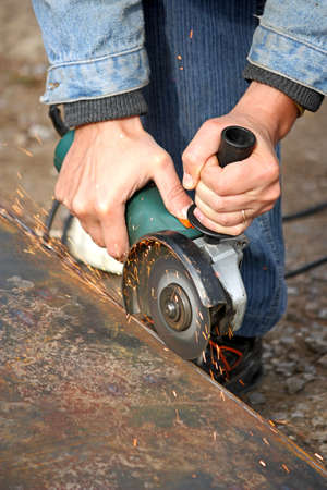 A worker cuts a metal by grinding wheel. Vertical photo photo