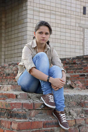 ordeal: Resentful young woman sitting on the destroyed wall of the building
