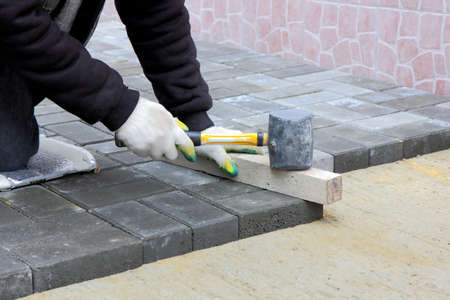 block of flats: Worker installs paving slabs in the courtyard Stock Photo