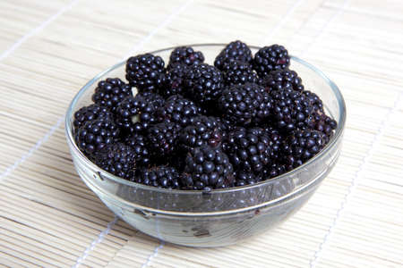 Glass bowl with ripe blackberries on mat of straw