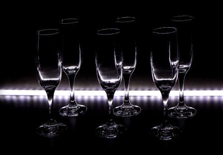 Wine glasses with light on black background