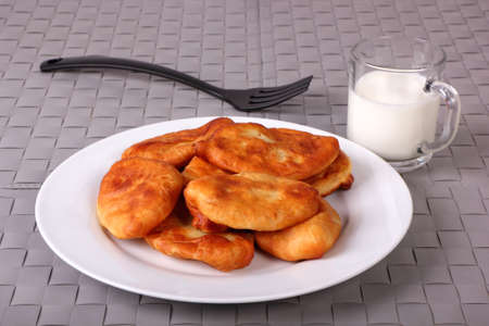 Fried cakes on white plate, fork and cup of milk on gray wicker background