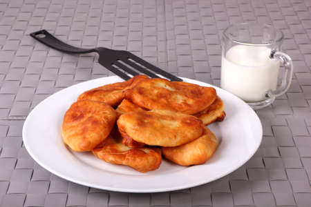 Fried cakes on white plate, plastic spatula and cup of milk on gray wicker background