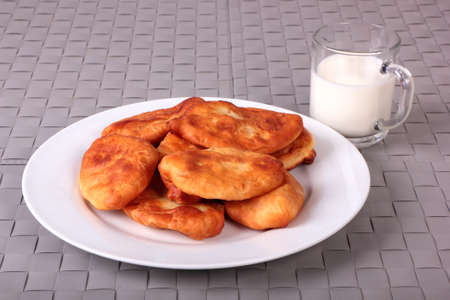 Fried cakes on white plate and cup of milk on gray wicker background Stock Photo