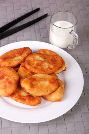 Fried cakes on white plate, kitchen tongs and cup of milk on gray wicker background. Vertical photo