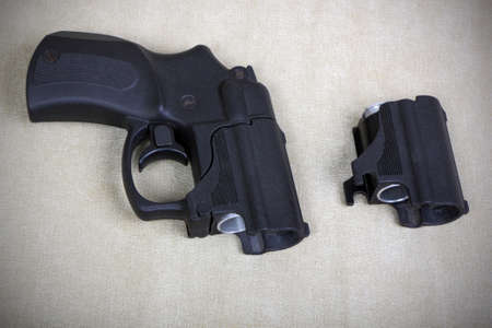 Tubeless doubly charged traumatic pistol and holder with two bullets. Image with vignette