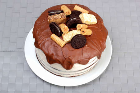 Cake, glazed with milk chocolate and decorated with waffles and cookies, on white plate