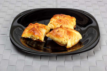 Envelopes of dough stuffed with mushrooms and chicken, baked in oven, on black plate