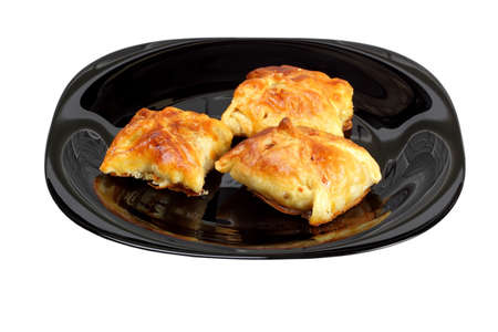 Envelopes of dough stuffed with mushrooms and chicken, baked in oven, on black plate. Isolated on white