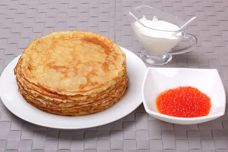 Pancakes, red caviar and sour cream on gray wicker background