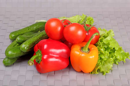 Cucumbers, tomatoes, paprika and lettuce leaves on gray wicker background