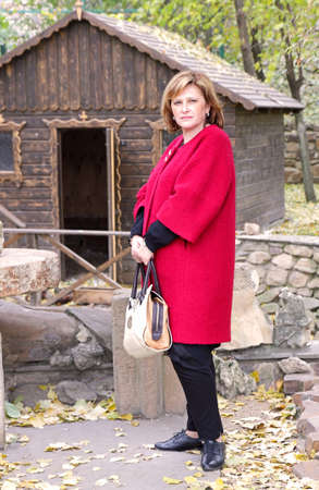 Adult woman in red coat standing in the autumn park and looking at the camera