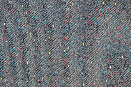 interspersed: Texture of coarse gray fabric with interspersed red, blue and yellow threads