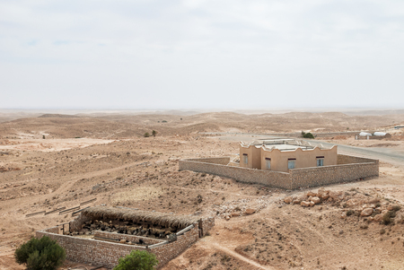 Sheepfold and a building in the middle of an arid desert with a horizon line Stock Photo