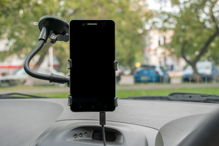 Smartphone with a clean black screen as a navigator mount to the windscreen of the car