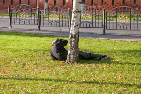 A drunkard lying on the grass wakes up on a sunny afternoon Stock Photo