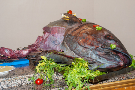 A huge semi-finished tuna lies on a table in a restaurant surrounded by spices and greens