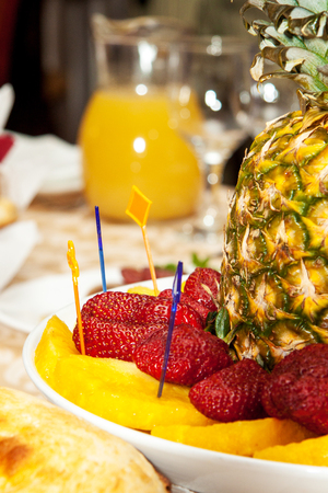 Luxuriously decorated table with pineapple and strawberries in the foreground