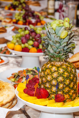 Luxuriously decorated table with tropical fruits, strawberries, bread and pineapple in the foreground