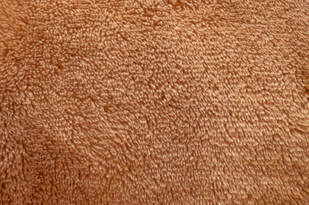 Texture of brown fluffy soft plush fabric consisting of many threads close-up