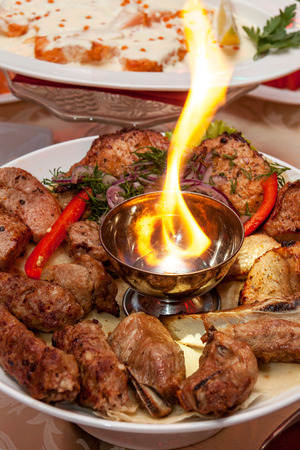 Luxuriously decorated table with roast meat and fire in the middle of the plate Stock Photo