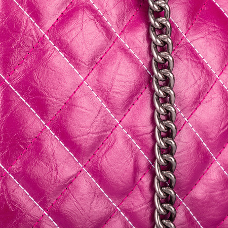 Purple leather textured material sewn with threads in the form of rhombus with a hanging metal chain