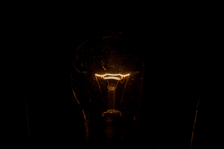 An old light bulb in complete darkness with a red-hot tungsten filament