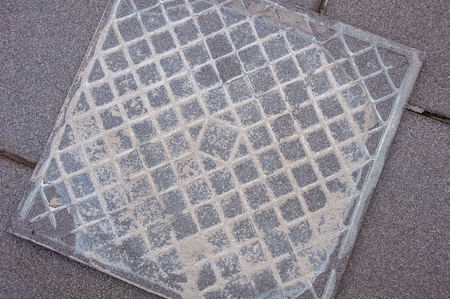 Inverted floor tile with traces of cement lying on the laid tiles