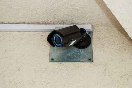 City CCTV camera with blue LEDs hanging on a rough house wall