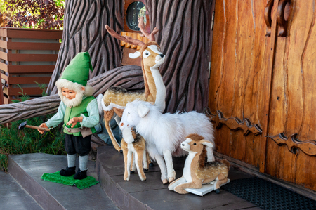 Dwarf, three deer and a sheep stand on the porch in front of the door