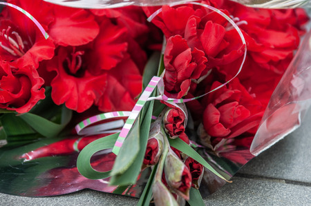 Bright bouquet of red gladioli tied with a decorative ribbon on a granite slab Stock fotó
