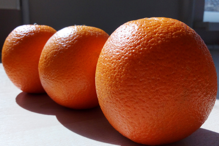 Three juicy oranges lie in a row on a table lit by the bright morning sun Stock fotó