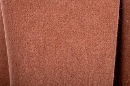 Texture of brown wool with orange shading. Not knitted, with beautiful folds. Top view close up