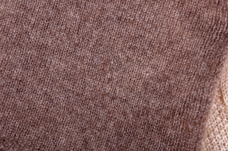 Texture of brown and beige knitted wool. Small knitting. Top view close up