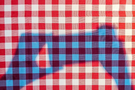 Checkered red and white cotton tablecloth on the table of a cafe or restaurant with a shadow from the hands holding a smartphone. Top view Stock fotó - 119027743