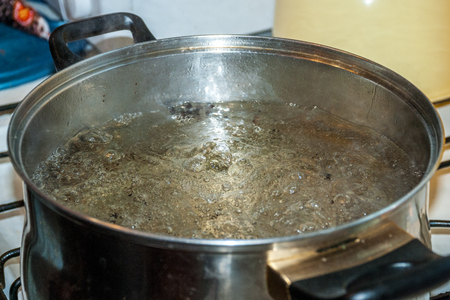 Boiling water for spaghetti or soup in a stainless steel pan on the kitchen stove at home Stock fotó