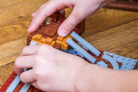 Hands of the child collect a house from the multi-colored plastic parts of the designer on a wooden parquet