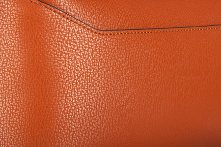 A piece of monochrome orange leather with neat stitching