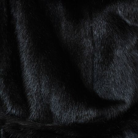 Texture of natural black shiny fur with beautiful wavy folds