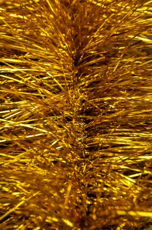 Sparkling yellow tinsel for a Christmas tree. Blurred foreground