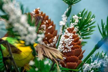 Artificial brown cone sprinkled with snow on a handmade green Christmas tree with blurry front needles Stock fotó