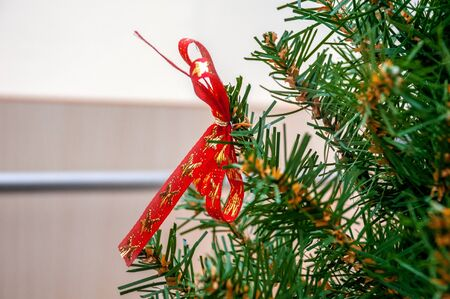 Christmas decoration red bow with gold embroidery on a fluffy green spruce branch. Horizontal frame Stock fotó