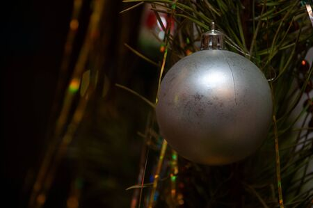 Old silver christmas ball on spruce branch close-up. Background for greeting card.