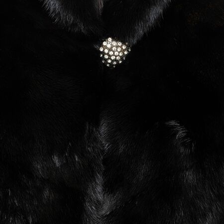 Texture of natural black shiny fur with beautiful wavy folds and a sparkling button on top