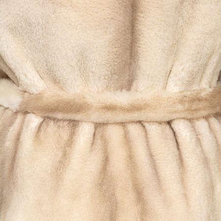 Texture of natural light gentle beige fur with belt closeup