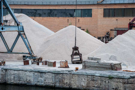 Port work: loading and unloading large piles of sand and gravel