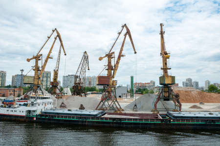 Port work loading and unloading the barge with sand and gravel Standard-Bild