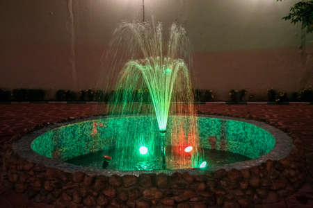 A multicolored fountain lit at night in a natural stone frame