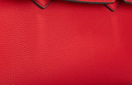 Part of a red leather female bag with a closed pocket flap and a good texture